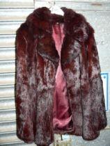A short fur Jacket in dark red/black, size M.