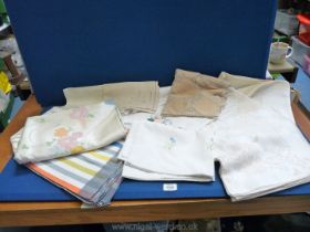 A box of vintage embroidered linen and lace tablecloths, etc.