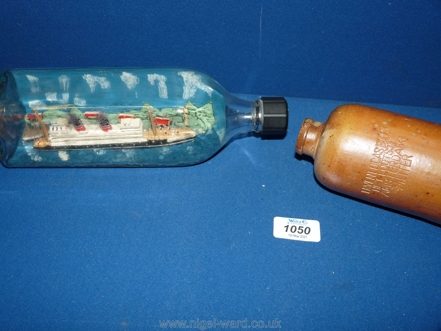 An old Ship in a bottle with painted hilly landscape behind; - Image 2 of 2