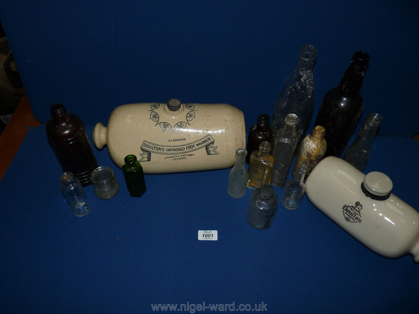 A quantity of bottles and two stoneware bed warmers 'Doulton's improved foot warmer'.