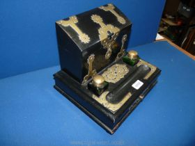 A brass bound ebonised stationery Desk Stand with two brass topped green glass inkwells,