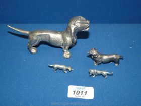 A family of white metal Dachshund ornaments plus one larger Dachshund.