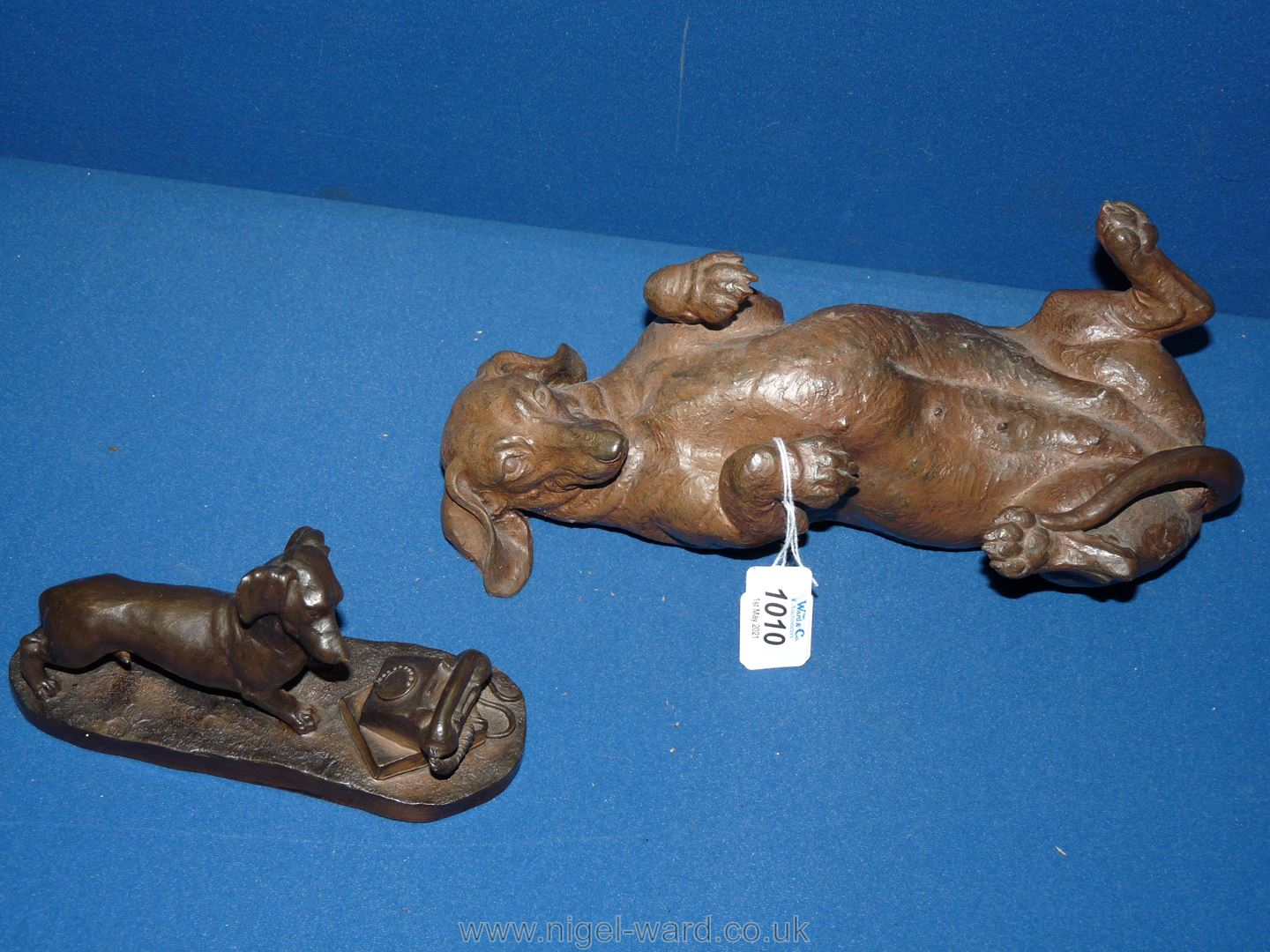 A heavy cast composite sculpture in a bronze patina of a rolling Dachshund,
