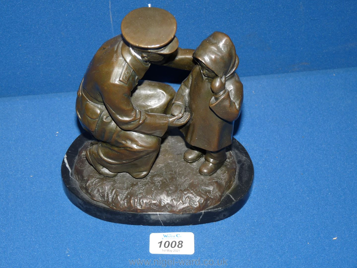 A Bronze figure of a soldier helping a young child, on marble plinth, 'H.