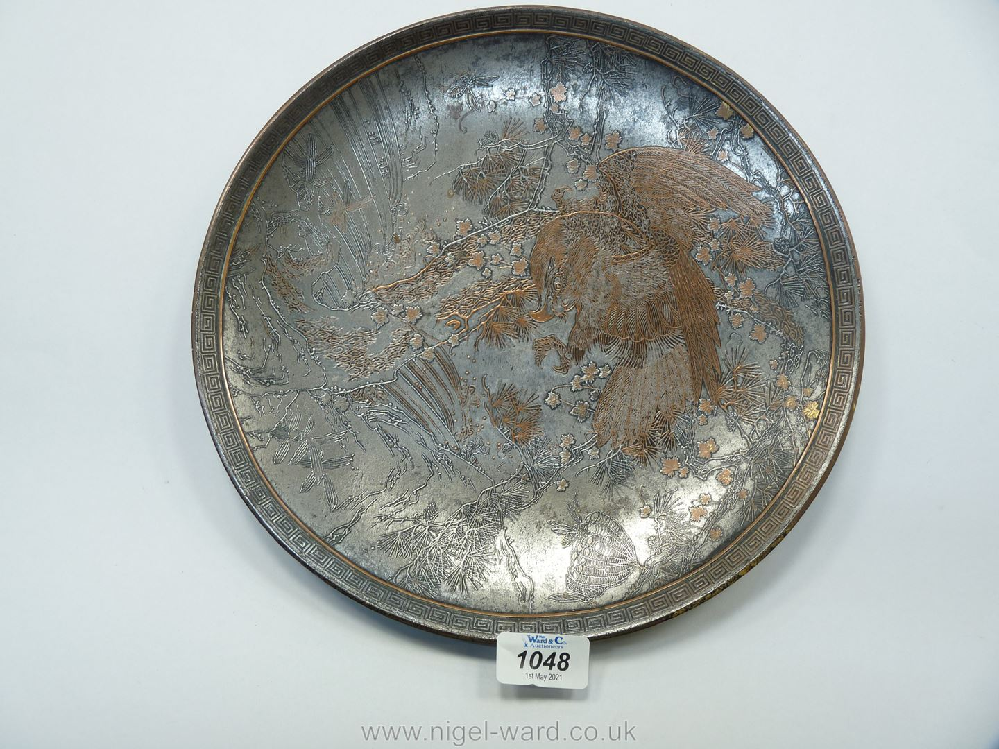 A Japanese iron Dish inlaid in copper with a design of an eagle among pine branches,