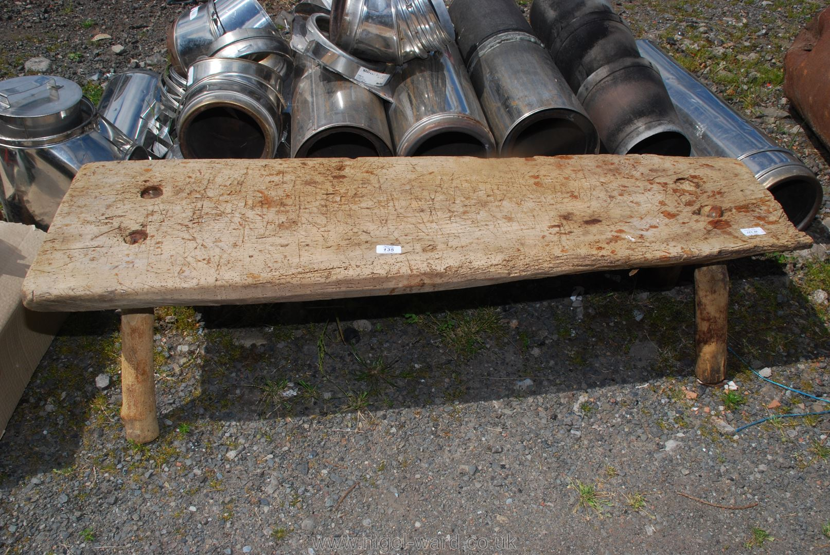 A Primitive oak Pig Bench, 38'' long, 14'' tall, depth varying from 12'' - 16''.