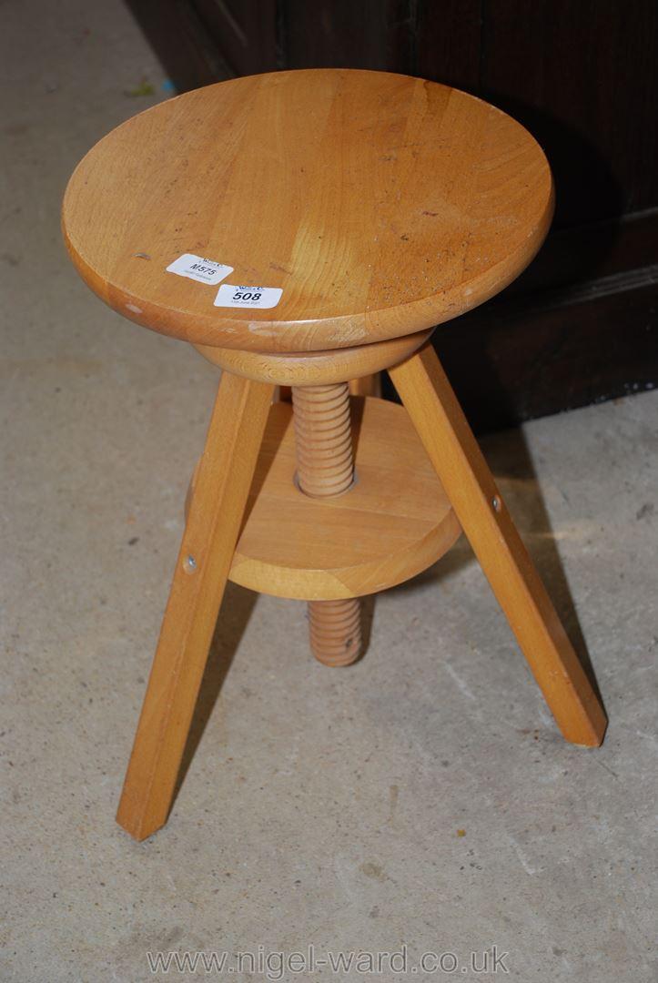 A circular adjustable pine stool.