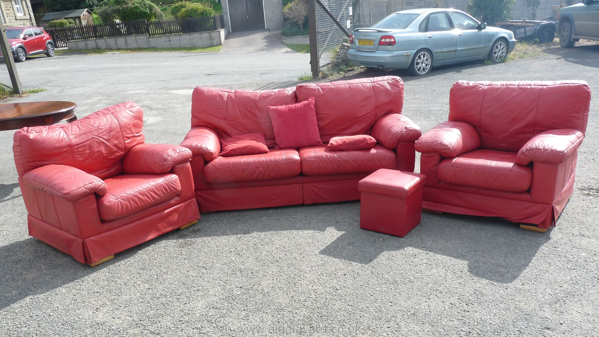 A red hide upholstered lounge suite comprising a three-seater settee and a pair of chairs.