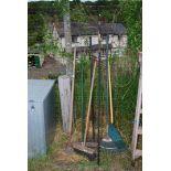 A quantity of garden rakes, broom, yard scraper, etc.
