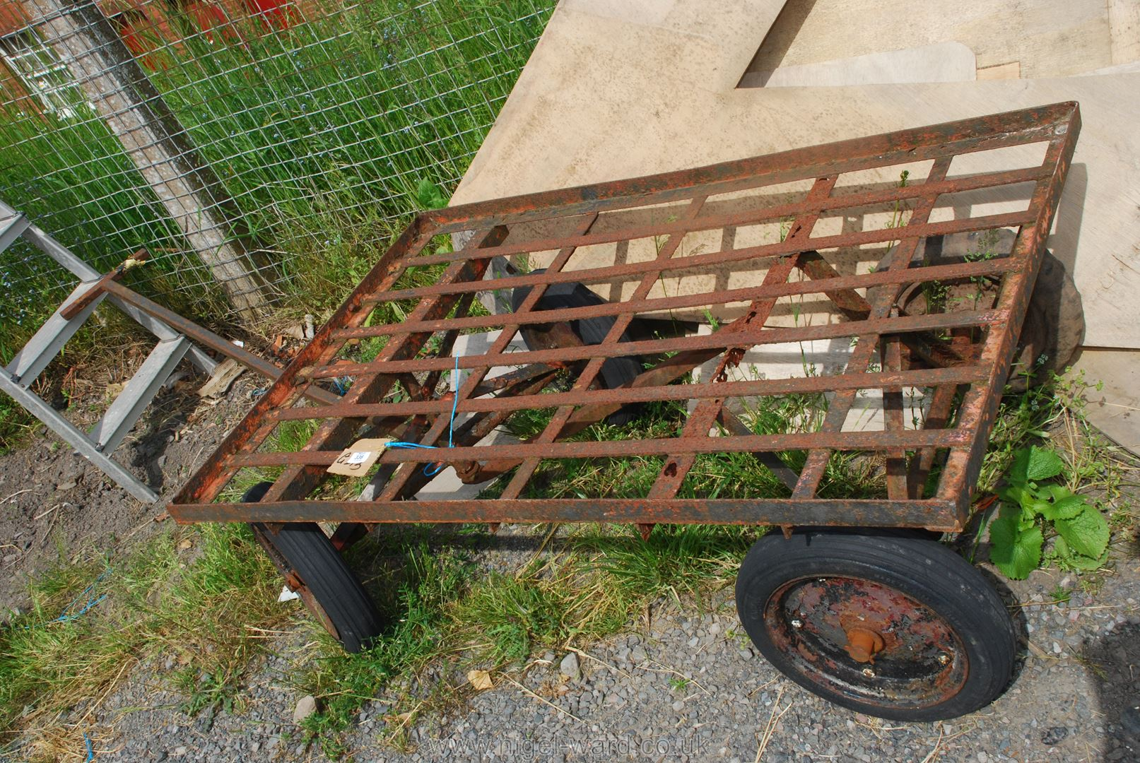 A metal framed four wheel Trolley on solid tyres, 48'' x 32''.