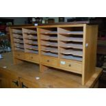A wooden stationery unit with four lower drawers.