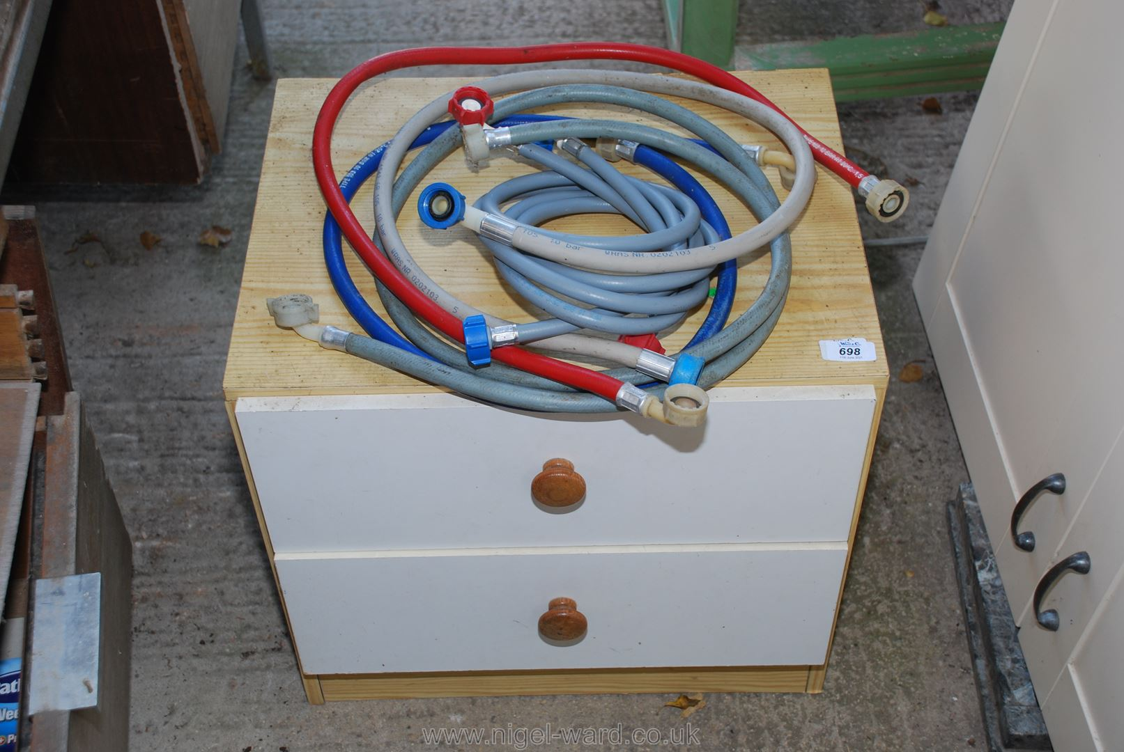 A bedside chest of drawers and a quantity of washing machine and dishwasher hoses etc.