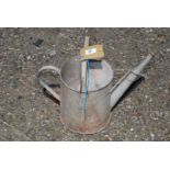 A small galvanized watering can.
