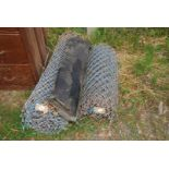 Two coils of chain link fencing and a part roll of roofing felt.