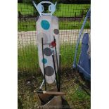 An ironing board, garden plant stand, walking stick, bird feeders and rounders bat.