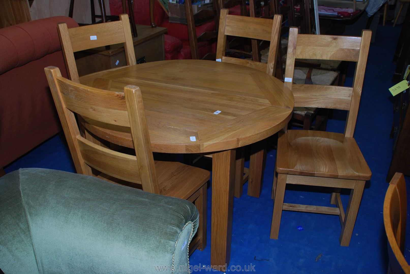 """A 43"""" diameter circular kitchen table and four matching chairs."""