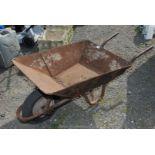 A metal Wheelbarrow on pneumatic tyre.