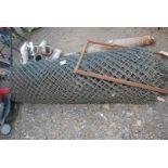 A large roll of plastic coated 6' high chain-link Fencing.
