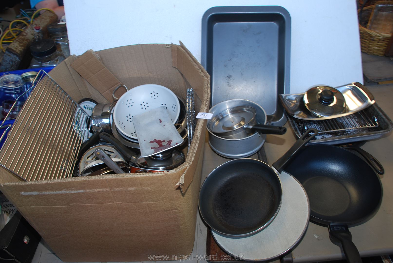 A box of kitchenware including a wok, roasting tin etc.