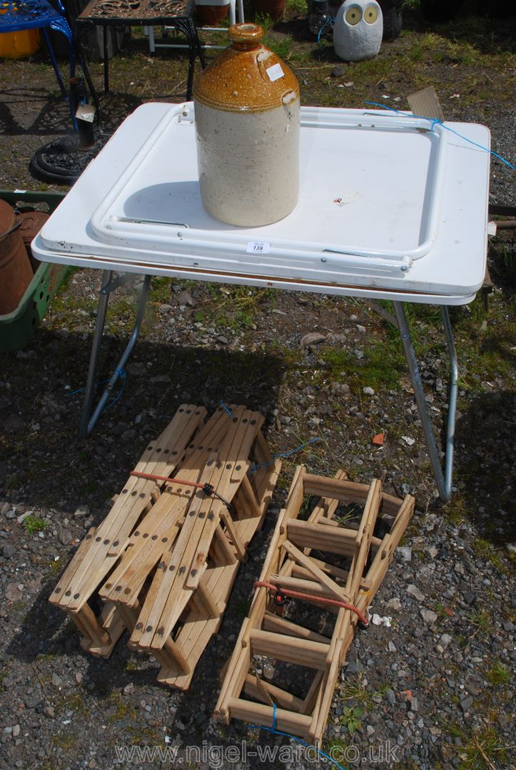 Five folding wooden wine racks, two folding camping tables and a stoneware cider flask.