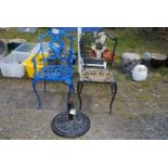 Two painted metal patio chairs and a parasol base.