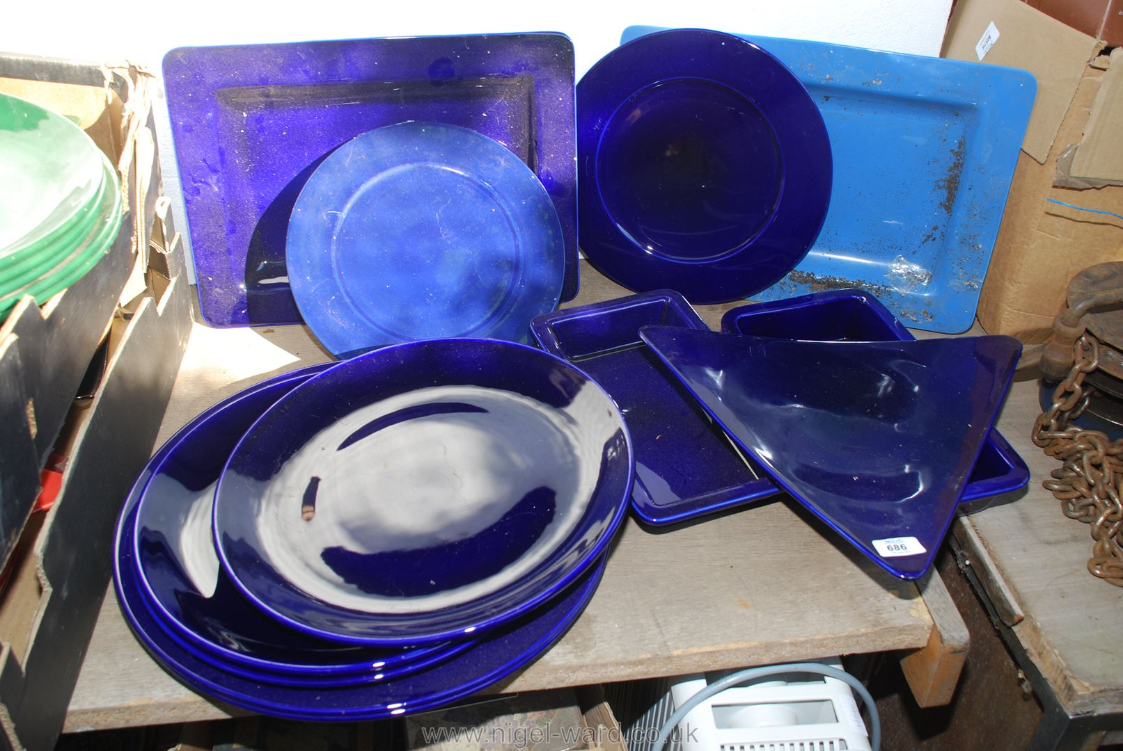 A quantity of large blue various shaped platters.