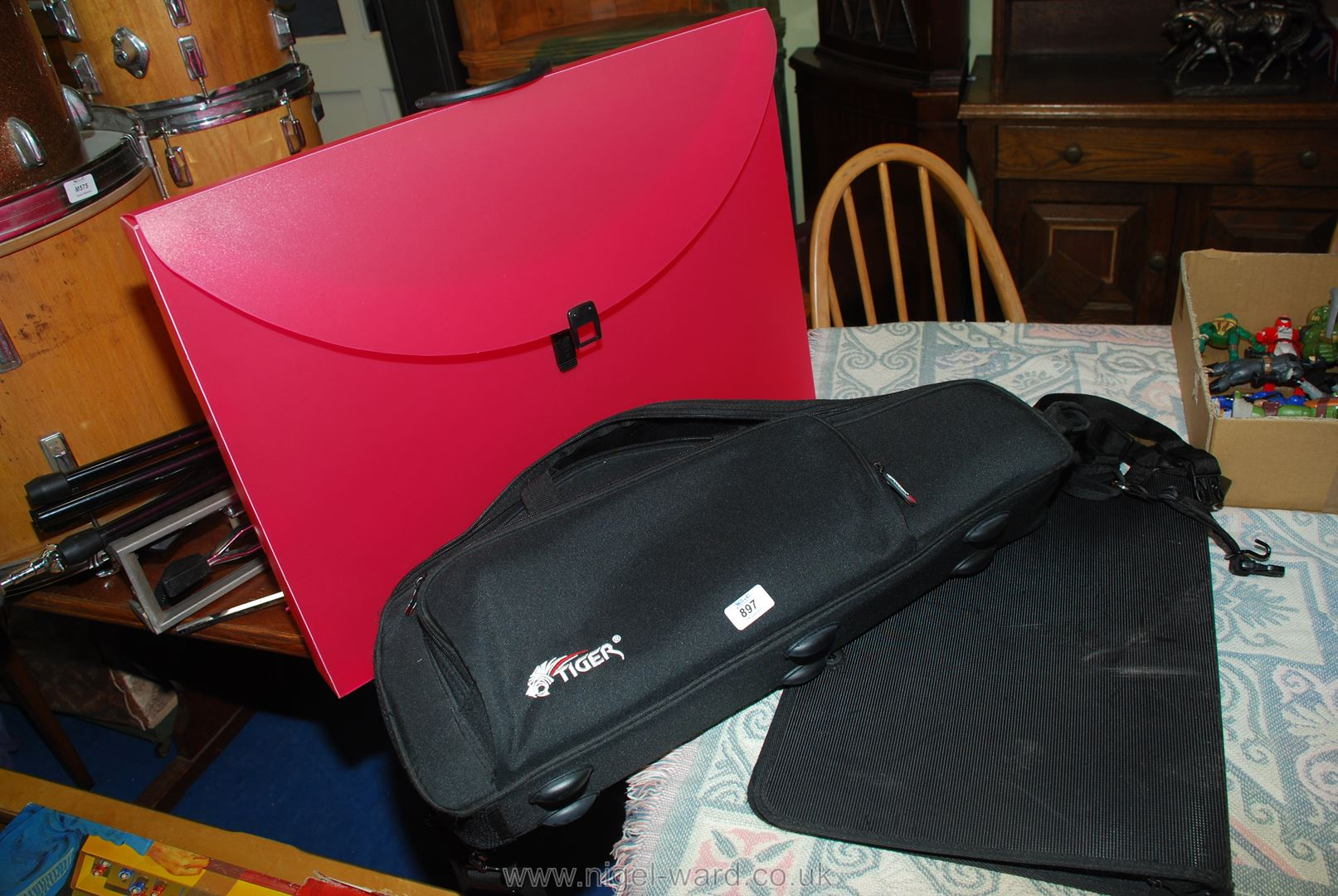 A Saxophone case and two portfolio cases.
