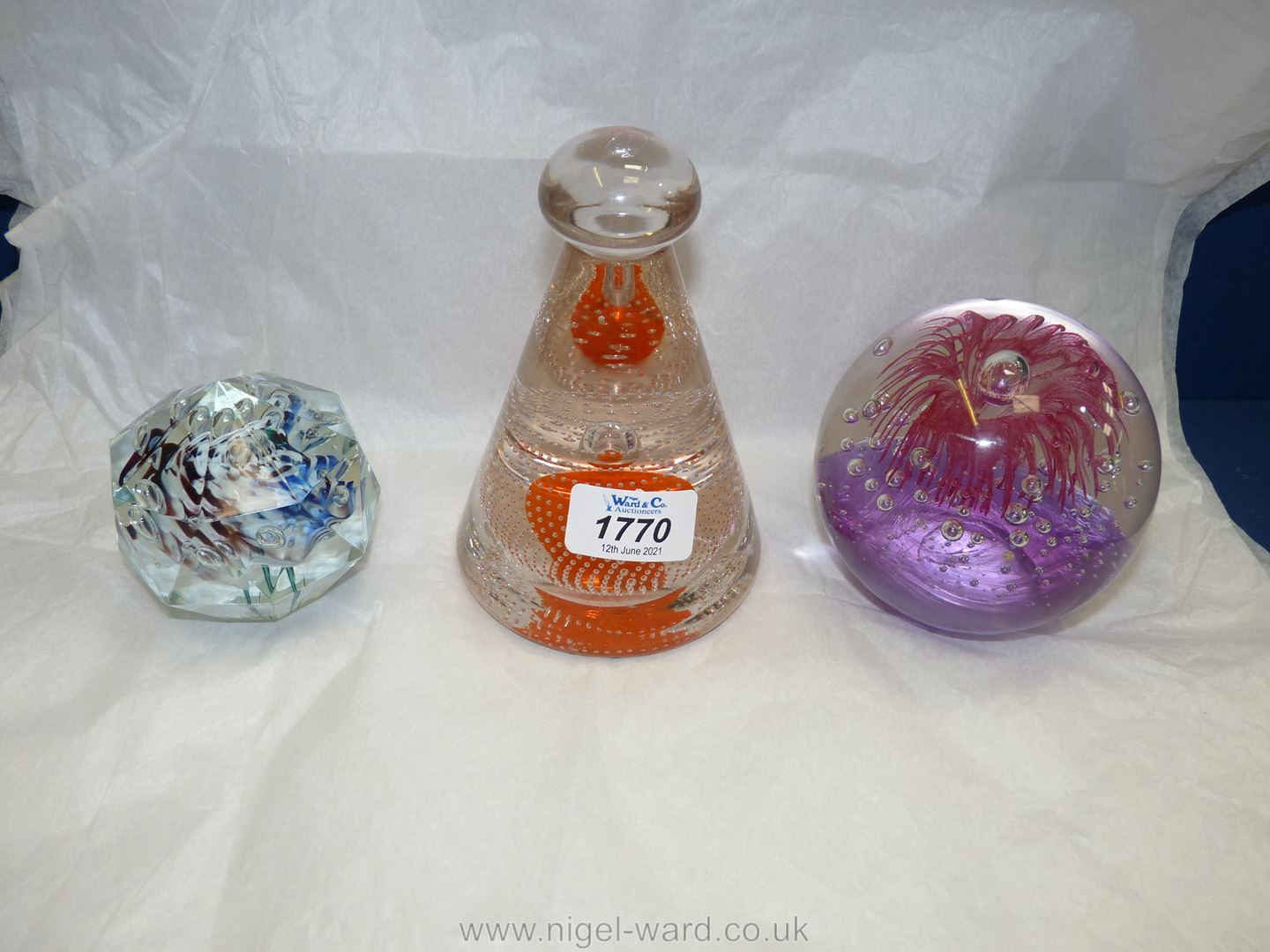 Three paperweights, one with dimple bottom and bubbles,