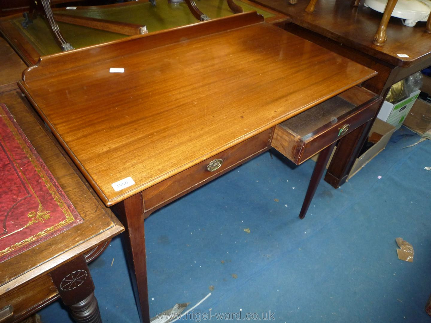 An Edwardian Mahogany side Table standing on tapering square legs and having a 2'' upstand and two