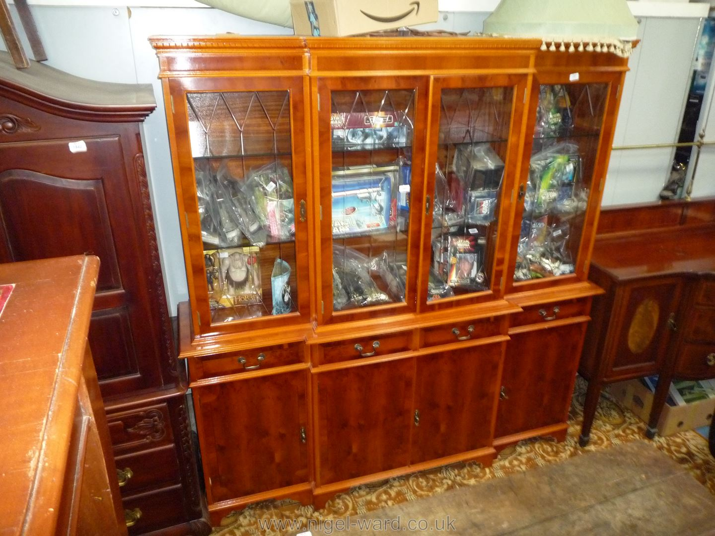 A contemporary breakfront Yew-wood finish Display Cabinet over a base with four doors and four