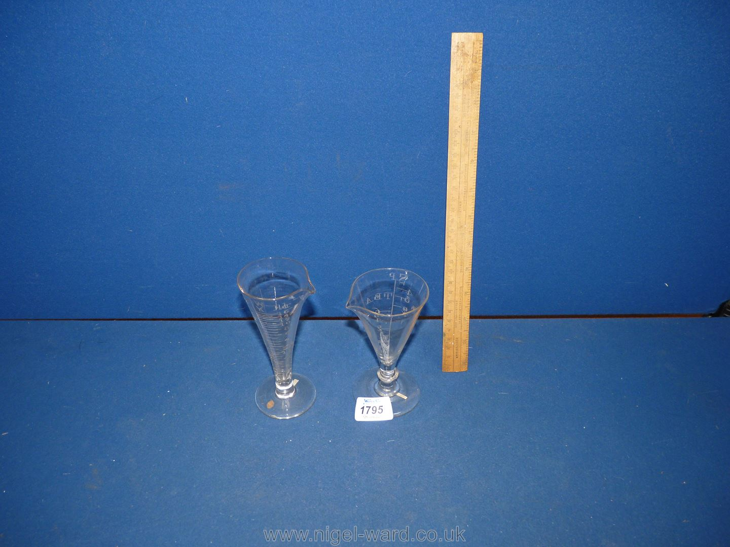 Two scarce Georgian funnel shaped chemist's measuring glasses, one circa 1750 with elliptical knop,