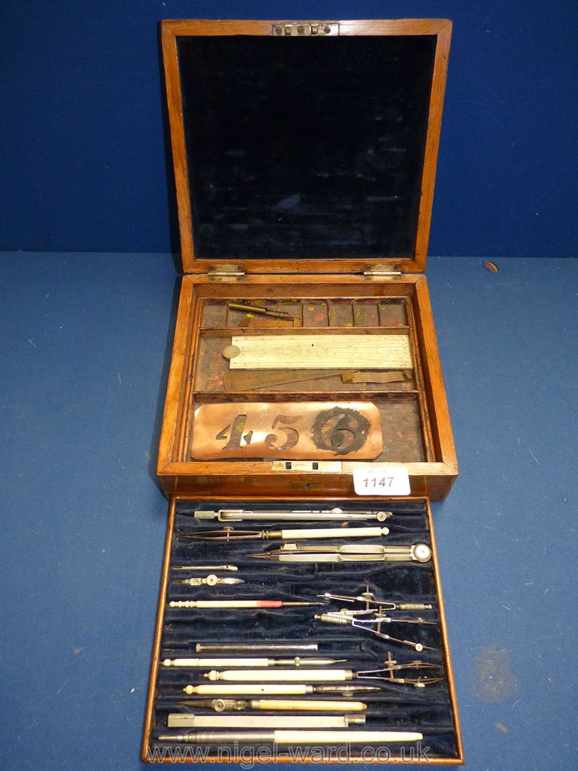 A brass cornered cased set of Drawing instruments with bone handles and lower tier with rulers, etc.