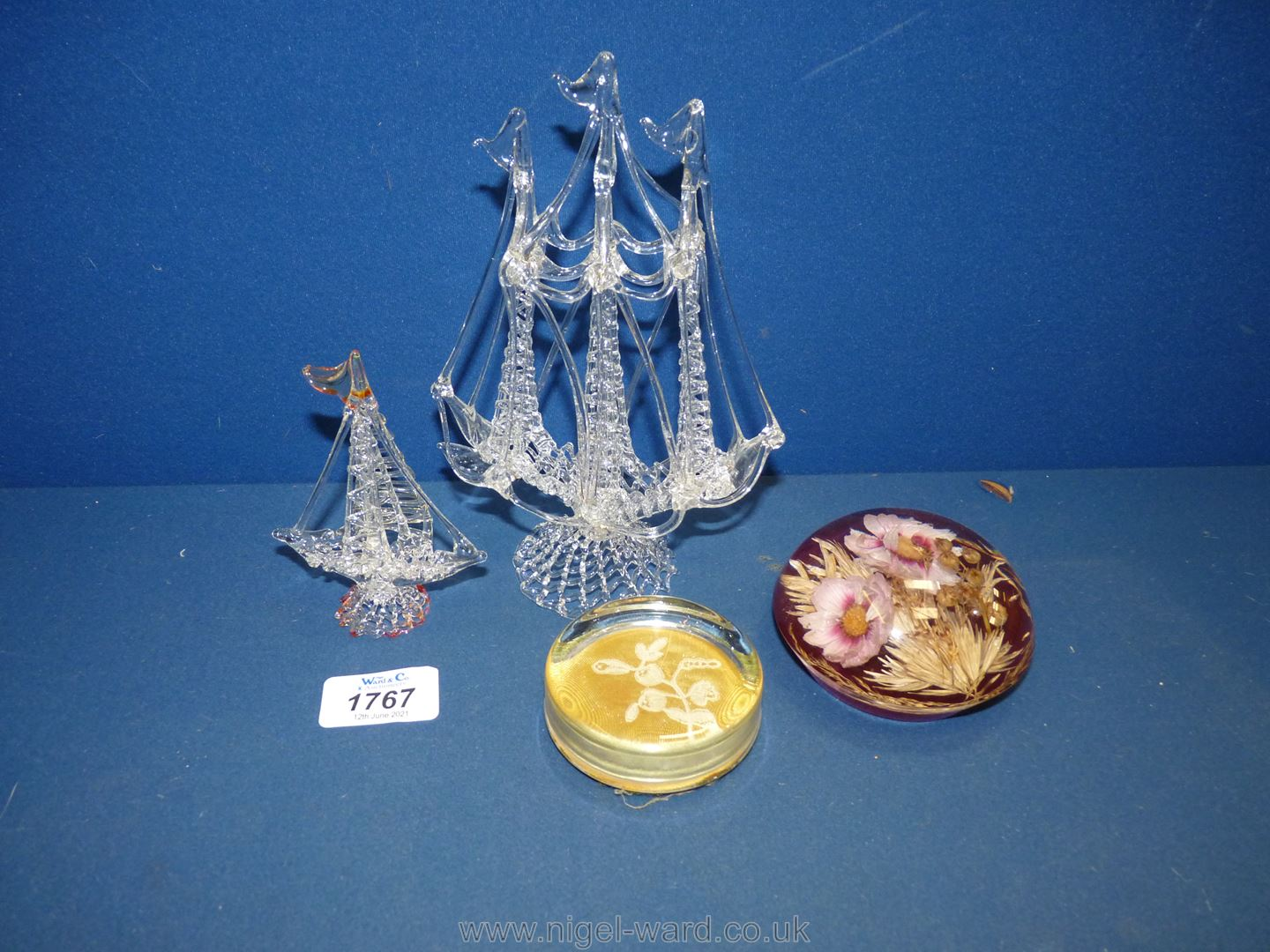 A spun glass model of a tall ship plus smaller one and two paperweights.