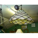 A large Tiffany style ceiling light shade on chain in iridescent yellow, slight damage.