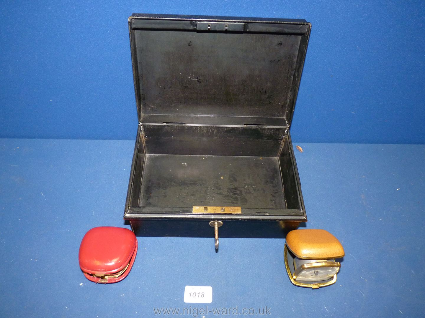 A metal Deed Box with key, and holding two cased travelling alarm clocks.