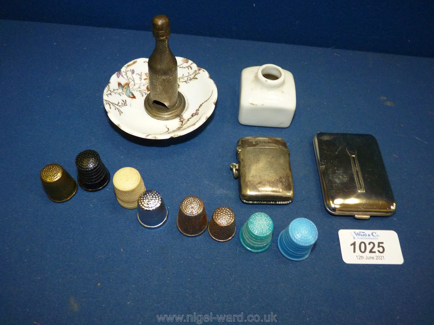 A cigar Cutter in the form of a bottle of champagne in a ceramic dish, seven thimbles,