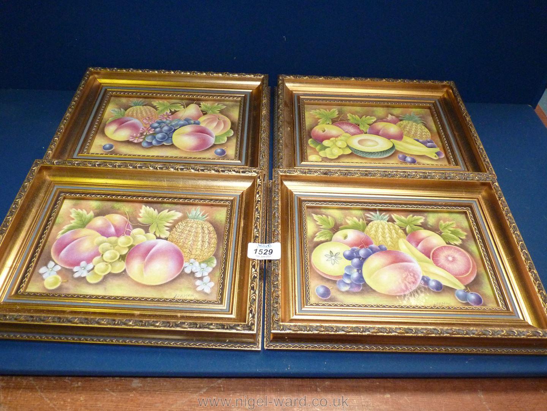 Four gilt framed ceramic tiles depicting pineapple, peaches, grapes, melon and grapefruit,