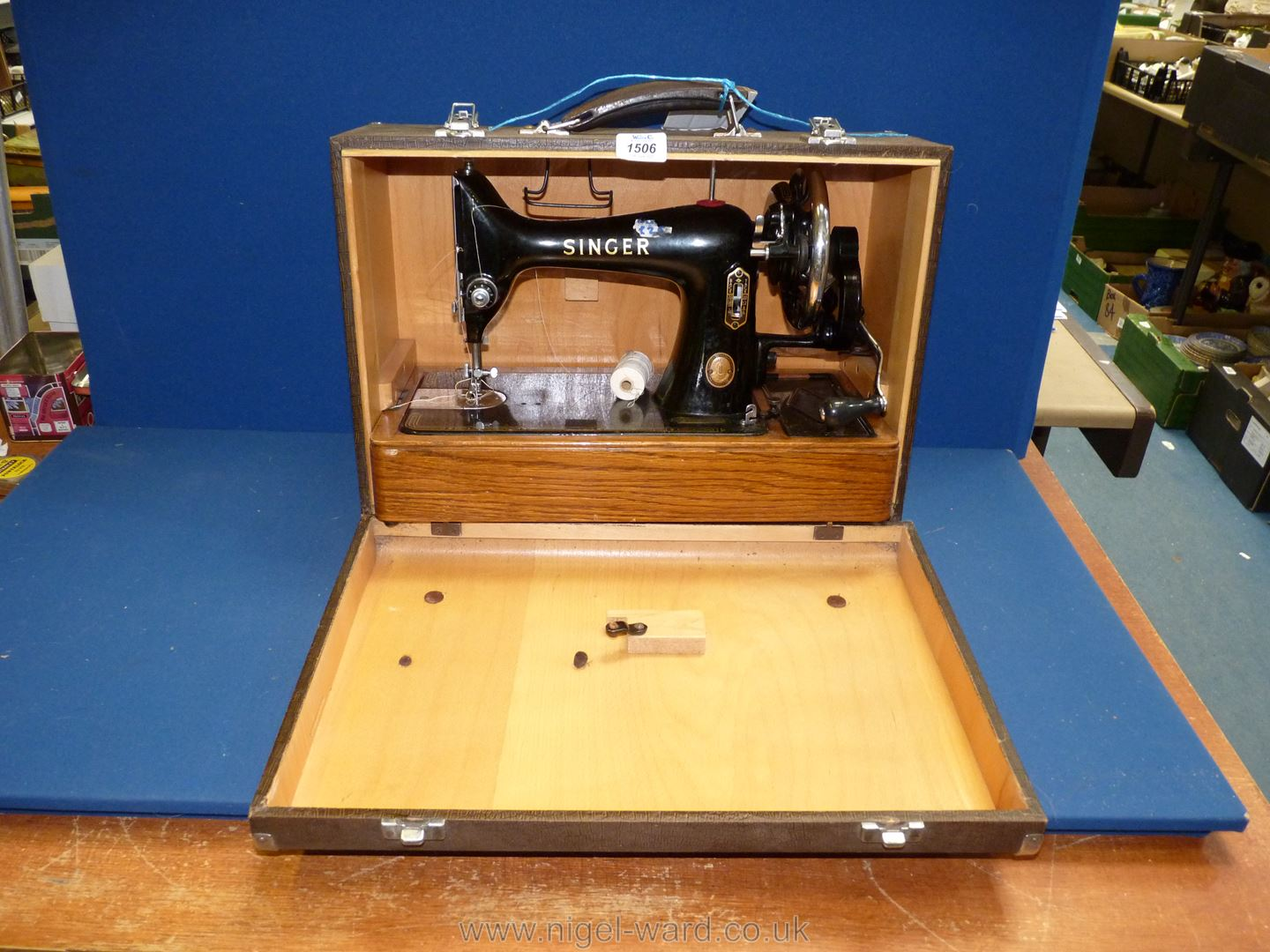 A hand turn, cased Singer sewing machine, No. EJ265028, working, good condition.