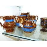 A lustre three Teaset and three lustre jugs with blue bands and one with raised floral detail,