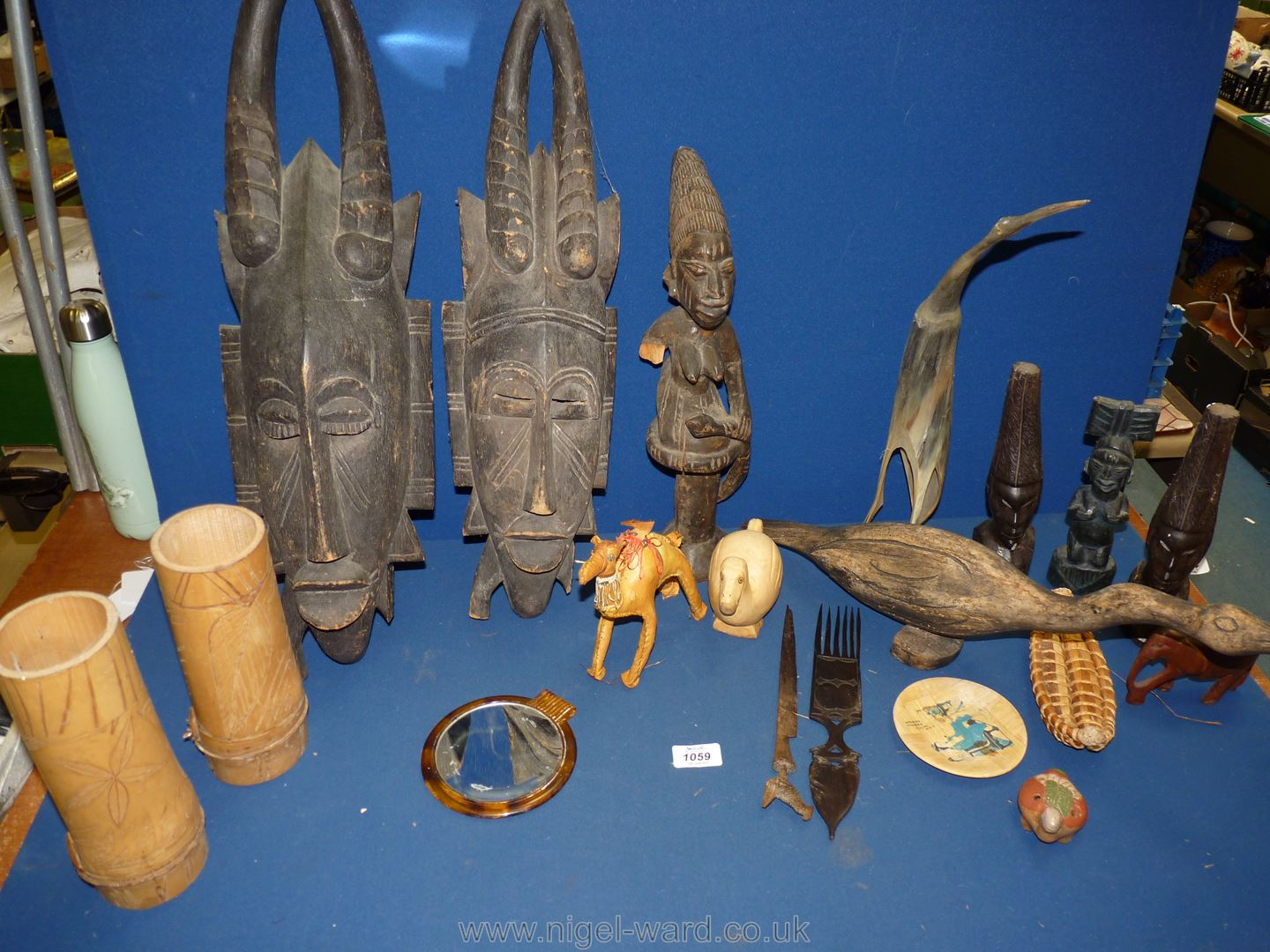 A box of African carvings to include two face wall hangings, bamboo beakers, horn carving of a bird,