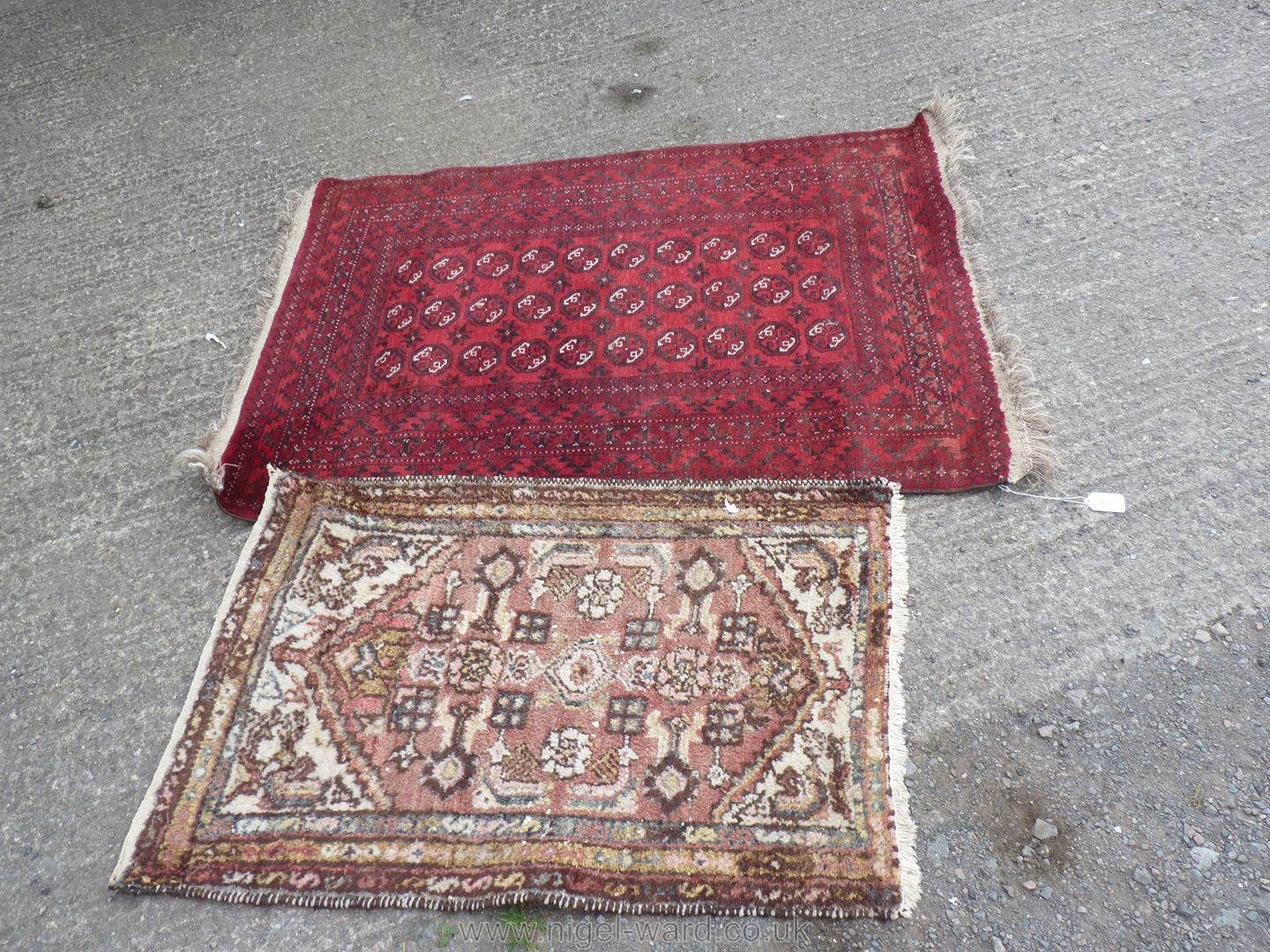 A burgundy ground bordered, patterned and fringed wool Rug with geometric pattern,