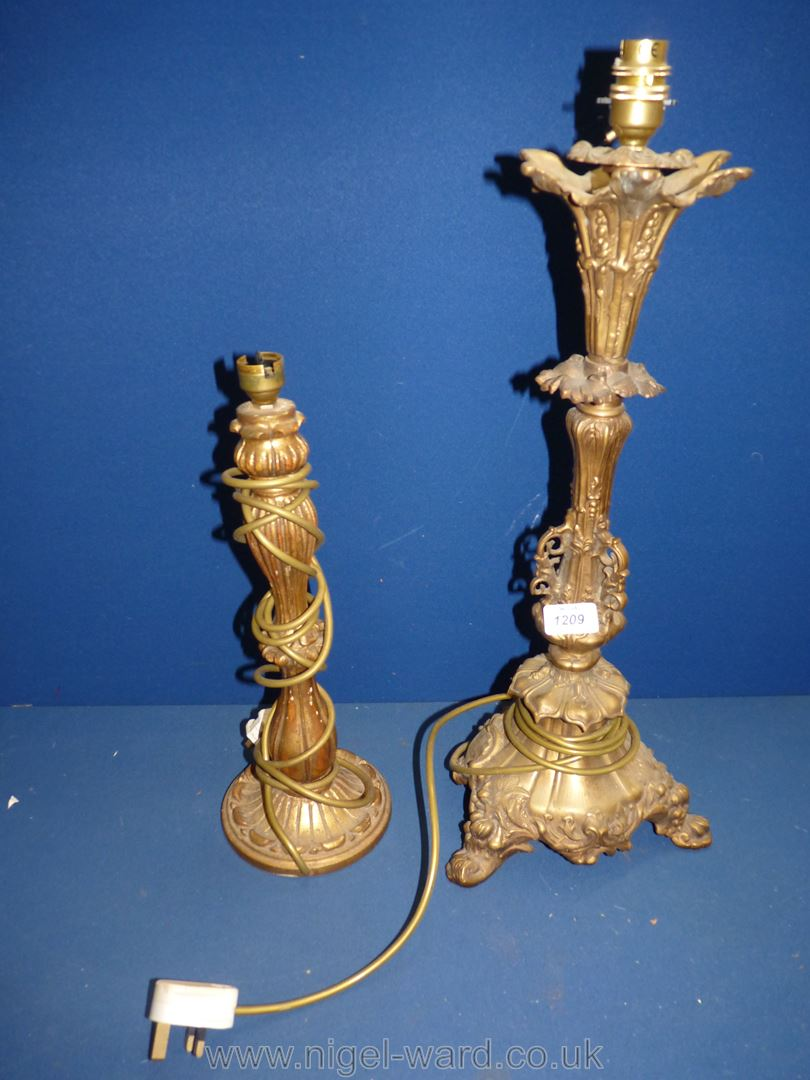 A heavy ornate Brass ornate electric table Lamp standing on three feet with scroll detail and leaf