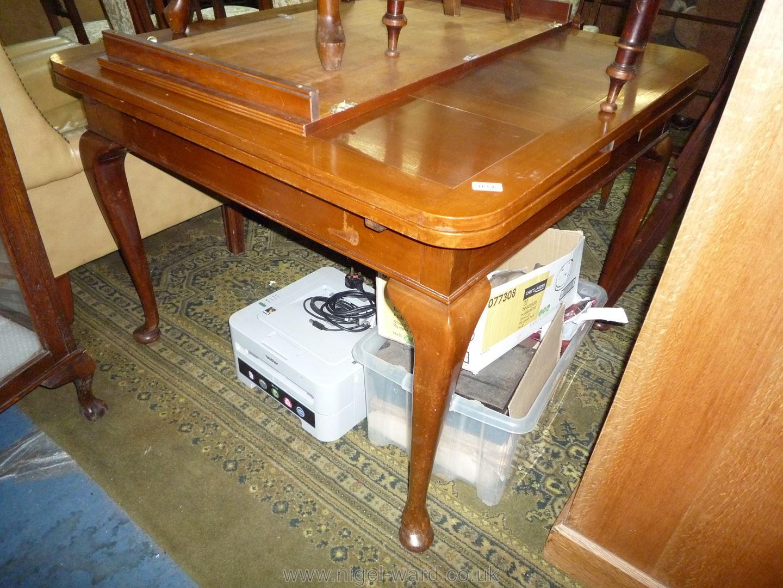 A Mahogany draw-leaf Dining Table standing on elegant cabriole legs,