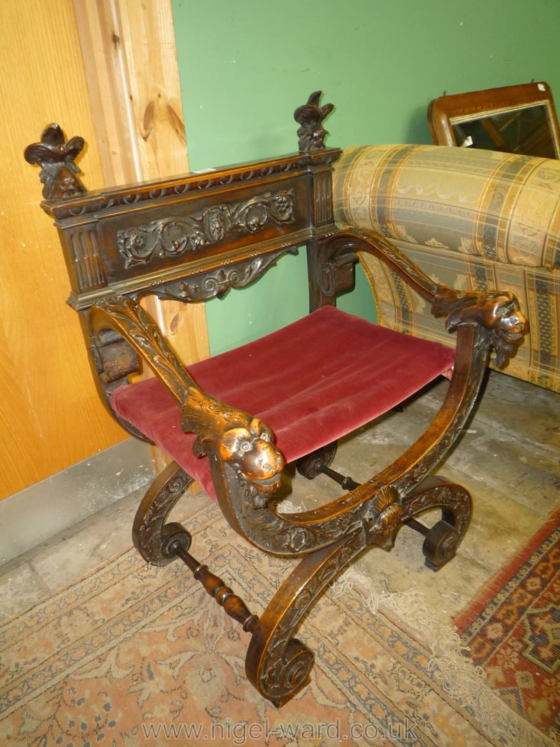 An elegant Mahogany 'X' framed open armed Armchair having carved and blind fretworked decoration,