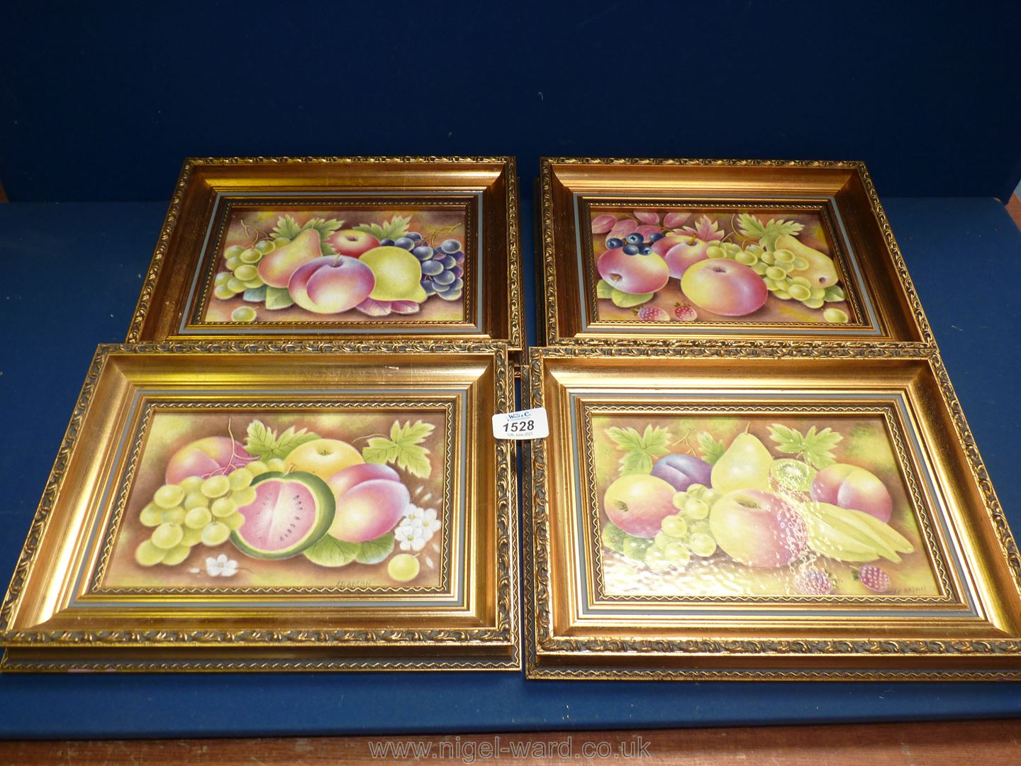 Four gilt framed ceramic tiles depicting apples, pears, white grapes and banana, after Leaman,