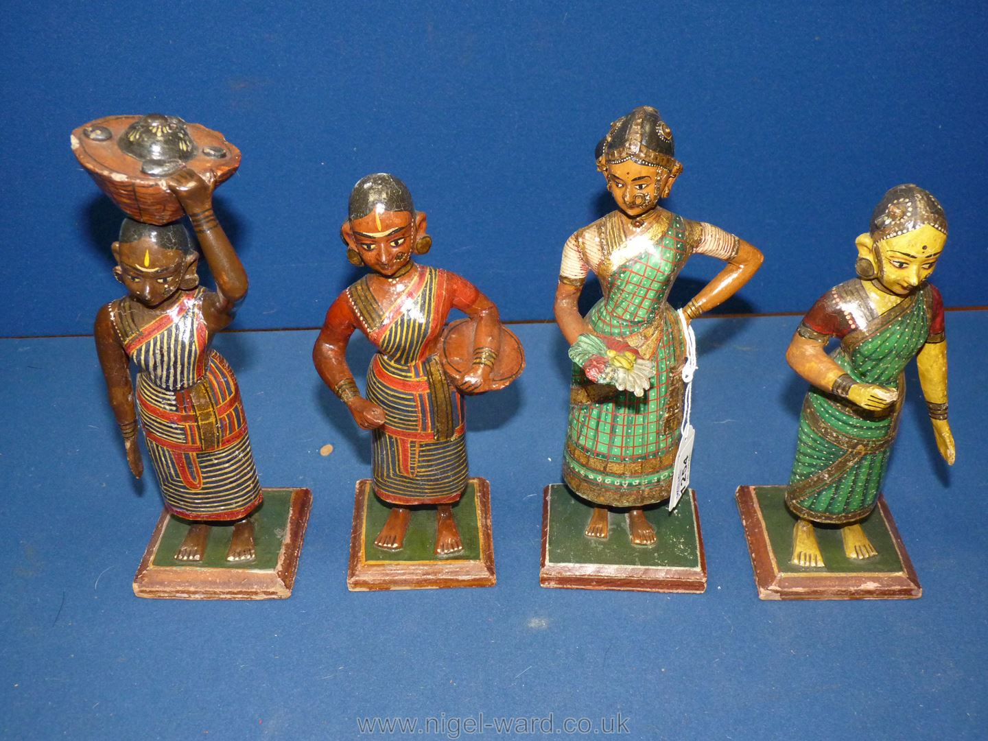 A set of four Indian carved and painted wood figures of lady market traders, circa 1900,