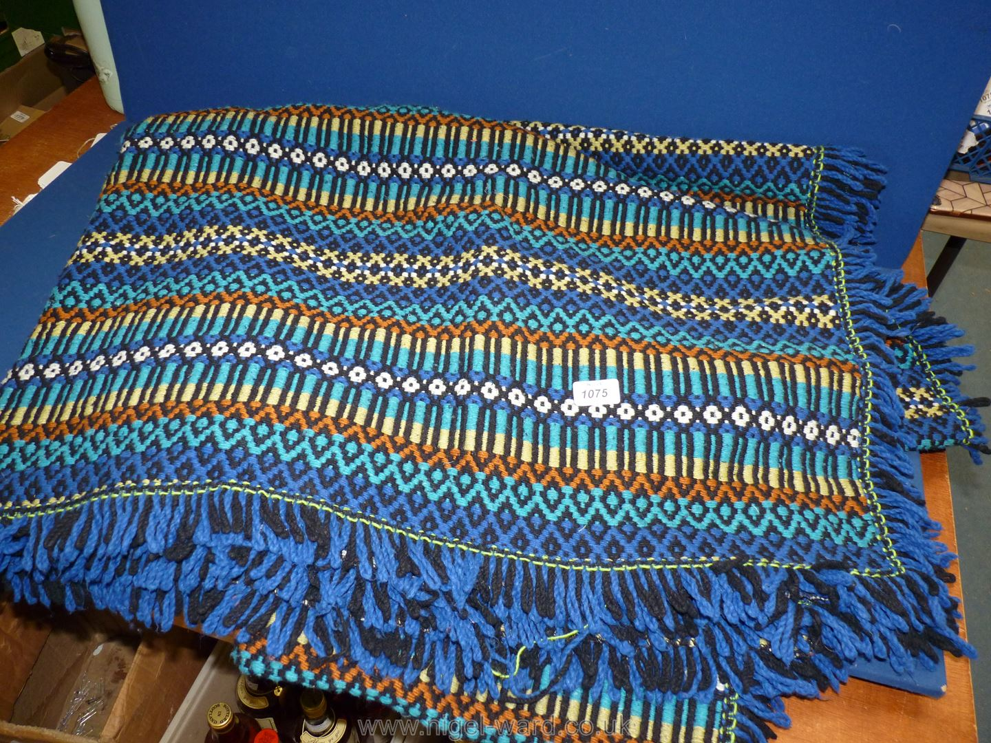 A large blue wool throw with fringing (some has come away).