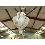 A hanging glass lamp shade in brown and white mottled tones with embossed rope decoration.