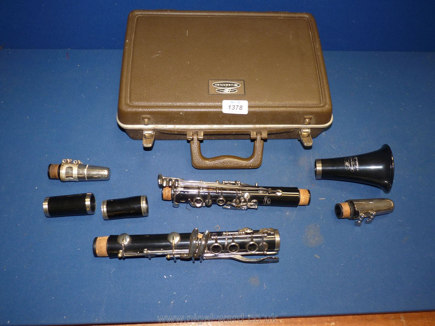A cased Buescher Aristocrat Clarinet having two mouth pieces, with cleaning rod and reeds.
