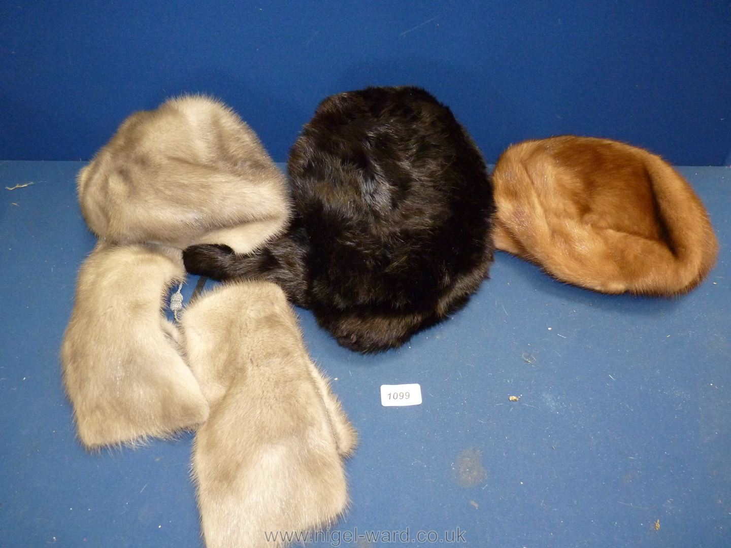 Three fur hats: one grey with scarf, one brown and black Trapper hat.